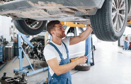 You can trust your car to us. Employee in the blue colored uniform works in the automobile salon.