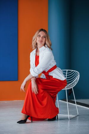 And its comfortable too. Beautiful blonde in festive red dress is in the room with orange and blue colored walls and white chair.