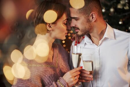 Sensual seduction. Nice couple celebrating new year indoors with classic beautiful clothes on they.