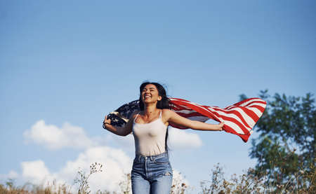 Female patriot runs with USA flag in hands outdoors in the field against blue sky.