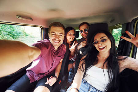 Young and cheerful people making a selfie inside a car. Having weekend.