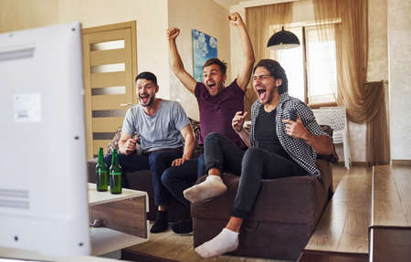 Celebrating victory. Excited three friends watching soccer on TV at home together.
