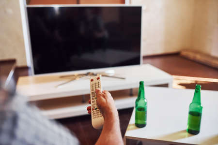 With beer on table. Backing view of man holds remote controller in hand and turning on TV. Stock Photo