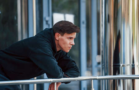 Portrait of young main in black clothes that leaning on the railings and taking a break. 版權商用圖片