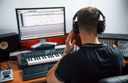 Sound engineer in headphones working and mixing music indoors in the studio. Stockfoto