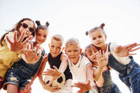Hello, gesture. With soccer ball. Portrait of kids that standing together and posing for the camera. Standard-Bild