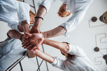 View from below. Successful business people putting their hands together.