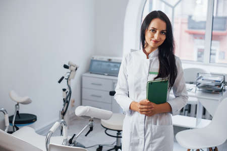 Brunette female doctor stands in modern office and looks at camera. Banque d'images