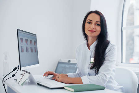 Brunette female doctor sits in modern office by computer and looks at camera.