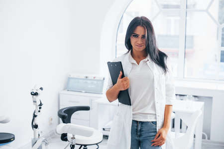 With notepad in hands. Brunette female doctor stands in modern office and looks at camera.