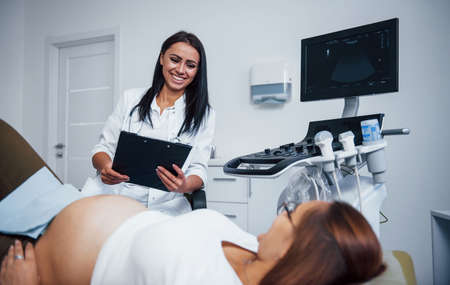 Female doctor talks about results of ultrasound for a pregnant woman in the hospital.