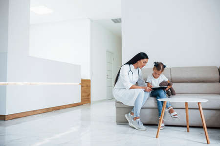 Female doctor with notepad sits in the clinic with little girl.