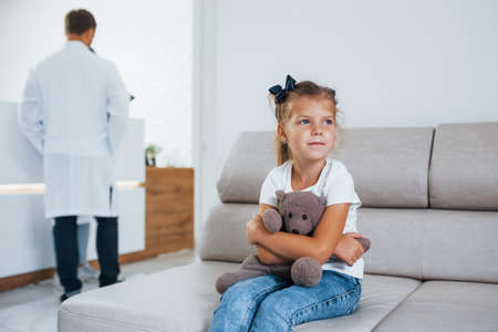 Doctors behind. Cute little girl with teddy bear in hands sits in waiting room of hospital.