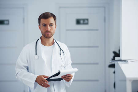 Portrait of confident male doctor with stethoscope and documents that stands in the clinic.
