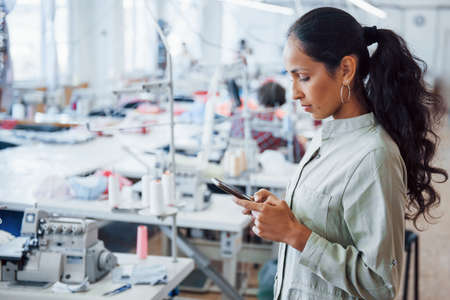 Woman dressmaker stands in the factory with phone in hands.