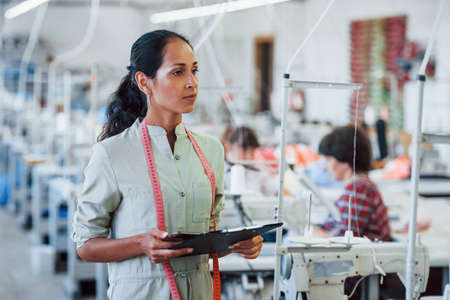 Brunette dressmaker works in the factory and holds notepad in hands.