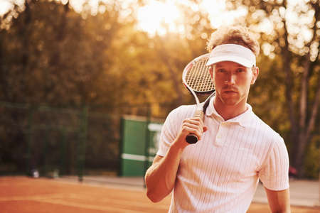 Beautiful sunlight. Young tennis player in sportive clothes is on the court outdoors.