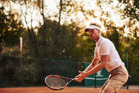 Photo in motion. Young tennis player in sportive clothes is on the court outdoors.