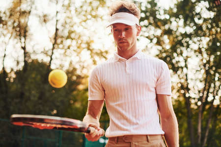 Young tennis player in sportive clothes is on the court outdoors.