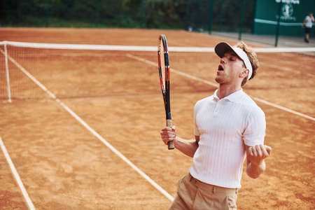 Celebrating victory. Young tennis player in sportive clothes is on the court outdoors.