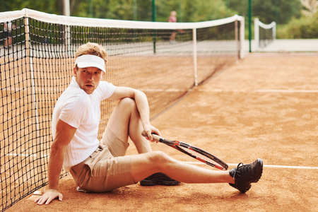 Tired tennis player in sportive clothes is on the court outdoors leaning on the net. Banque d'images