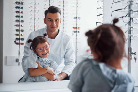 Young pediatrician in white coat helps to get new glasses for little girl.