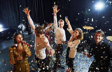 Confetti is in the air. Group of cheerful friends celebrating new year indoors with drinks in hands. Stockfoto