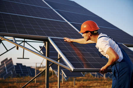 Manual work. Male worker in blue uniform outdoors with solar batteries at sunny day.