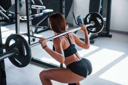Young fitness woman with slim type of body doing exercises by using barbell. Standard-Bild