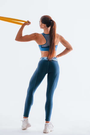 With yellow resistance band. Young woman with slim body type isolated against white background.