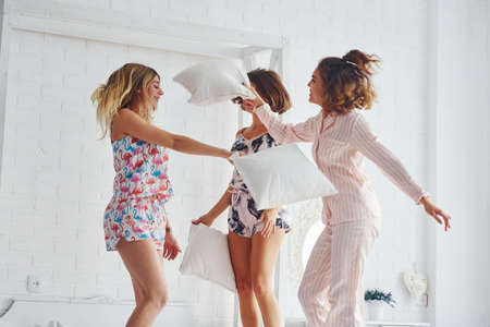 Pillow fight. Happy female friends having good time at pajama party in the bedroom.