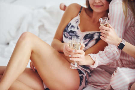 Celebrating with glasses of alcohol in hands. Happy female friends having good time at pajama party in the bedroom.