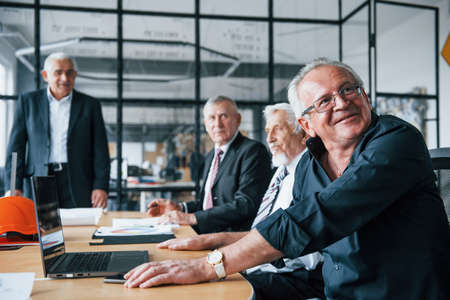 Aged team of elderly businessman architects have a meeting in the office. 免版税图像