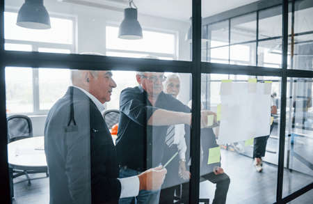 Working with stickers on glass. Aged team of elderly businessman architects have a meeting in the office. 免版税图像