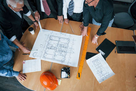Top view of aged team of elderly businessman architects have a meeting in the office and works with plan.