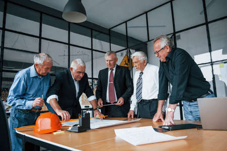 Planning construction by measuring it on paper. Aged team of elderly businessman architects have a meeting in the office.