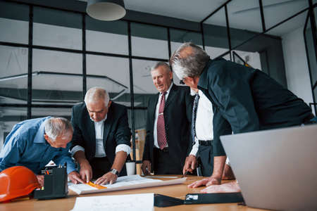 Aged team of elderly businessman architects works with plan in the office. 免版税图像