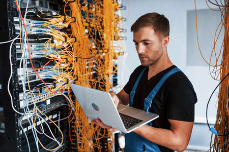 Young man in uniform and with laptop works with internet equipment and wires in server room.