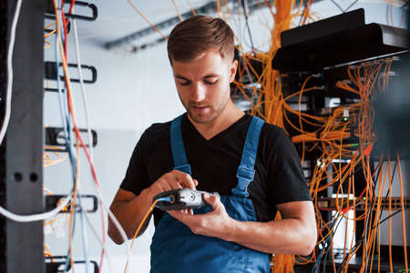 Young man in uniform with measuring device works with internet equipment and wires in server room.