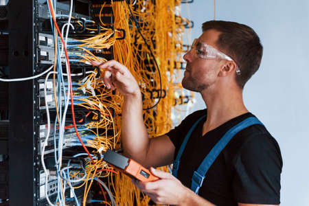 Young man in protective glasses works with internet equipment and wires in server room.