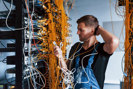 Young man in uniform feels confused and looking for a solution with internet equipment and wires in server room.
