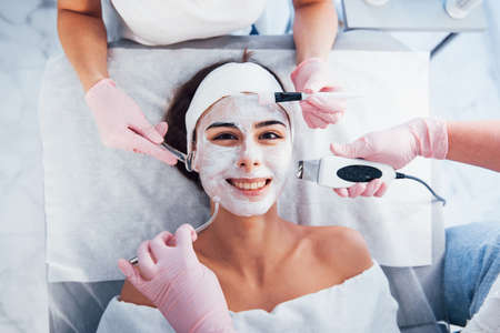 Close up view of woman that lying down in spa salon and have face cleaning procedure by different devices and mask.