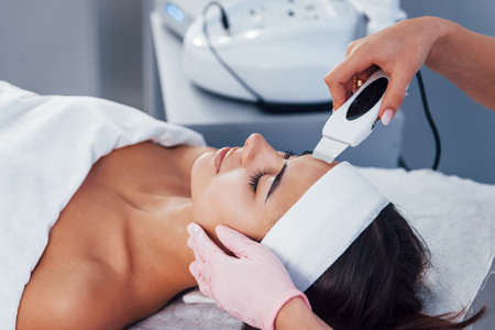 Using special device. Close up view of woman that lying down in spa salon and have face cleaning procedure.