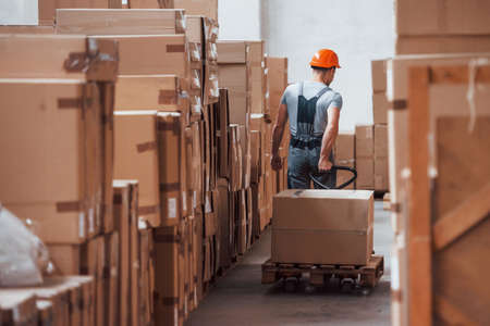 Young male worker in uniform is in the warehouse with pallet truck.