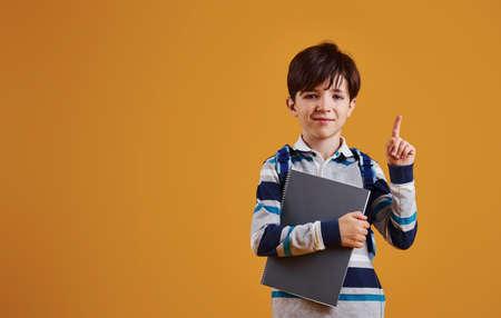 Portrait of young smart schooler in the studio against yellow background.