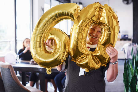 With balloons of number 60 in hands. Senior woman with family and friends celebrating a birthday indoors.