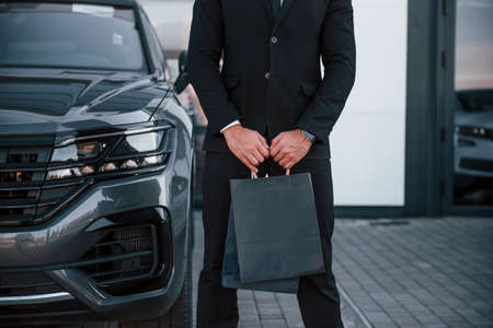 Close up view of businessman in black suit and tie stands near modern automobile with shopping bags in hands.