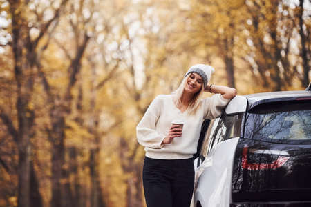 With cup of drink in hands. Girl have autumn trip by car. Modern brand new automobile in the forest.