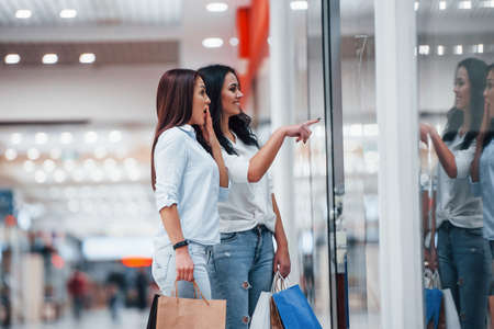 Looking through the glass. Two young women have a shopping day together in the supermarket.