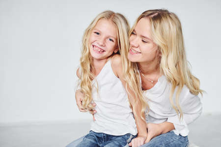 Closeness of the people. Mother with her daughter together in the studio with white background.